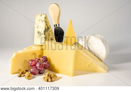Composition Of Different Types Of Cheese With Walnuts And Grapes On White Background. Blue Cheese Do