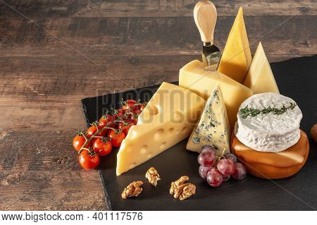 Collection Of Swiss, French, Italian And Holland Cheeses On A Black Cheese Board Served With Fruit,