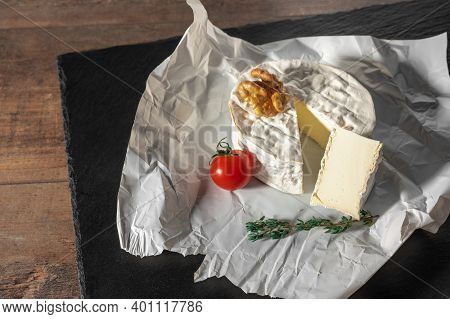 Delicious Brie Cheese, Walnuts And Tomato On Paper On Slate Black Background. Brie Type Of Cheese. C