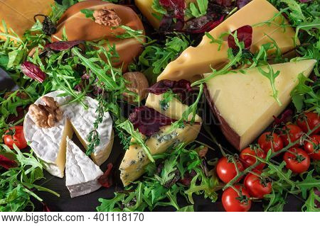 Cheese Background. Assortment Different Types Cheese With Walnuts, Tomato And Grapes On Black Slate