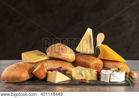 Cheese And Bread. Many Types Of Bread And Cheese On Brown Background. Cheese Platter, Tasting And Pa