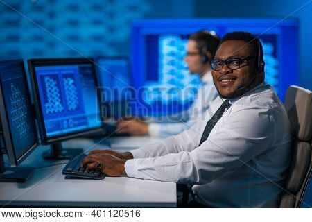Call-center worker is speaking with the client by headset. Workplace of the african-american support operator.