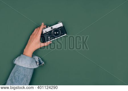 Female Hand Holding Old Retro Photo Camera On Green Background With Copy Space For Text. Trendy Vint