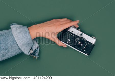 Closeup View Of Female Hand Holding Old Retro Photo Camera On Green Background With Copy Space For T
