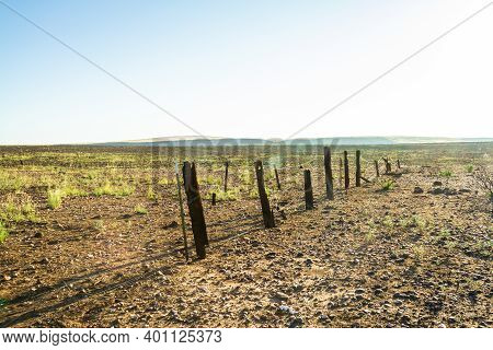Old Wood Fence With Fire Damage On A Flat Prairie Under A Blue Sky.