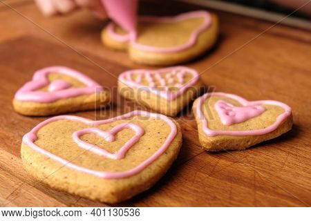 Icing Of Valentines Day. Woman Decorating Gingerbread Cookies In The Shape Of Heart On A Wooden Tabl