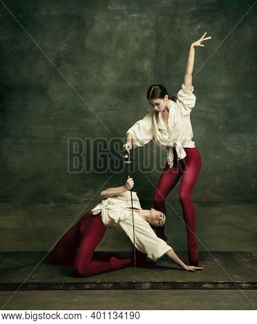 Action. Two Young Female Ballet Dancers Like Duelists With Swords On Dark Green Background. Caucasia