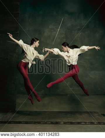 Fatal. Two Young Female Ballet Dancers Like Duelists With Swords On Dark Green Background. Caucasian