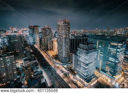 Aerial View Of Skyscraper Rooftops And Futuristic Skyline At Night With Vibrant Bright Lights In Tok