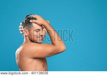 Handsome Man Washing Hair On Light Blue Background, Space For Text