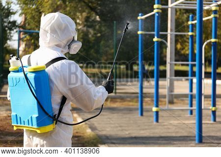 Person In Hazmat Suit Spraying Disinfectant Around Outdoor Gym. Surface Treatment During Coronavirus