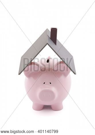 Pink piggy bank with house roof on white background