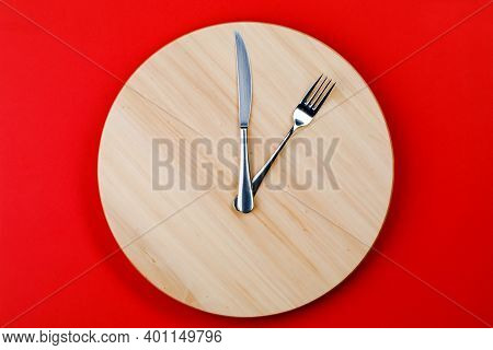 The Concept Of Intermittent Fasting And Skipping Meals. Wooden Round Tray With Cutlery In The Form O