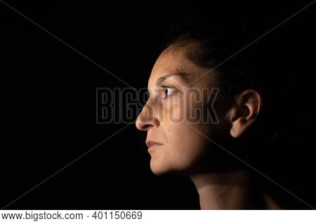 Dark Profile Portrait Of A Very Dimly Lit Woman. The Woman Is Looking Straight Ahead And Transmits S