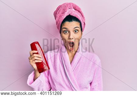 Young hispanic woman wearing shower bathrobe holding shampoo scared and amazed with open mouth for surprise, disbelief face
