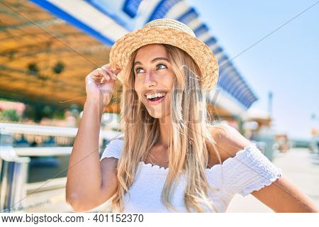 Young blonde tourist girl smiling happy looking to the side at fairground.
