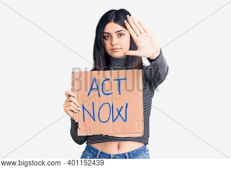 Young beautiful girl holding act now cardboard banner with open hand doing stop sign with serious and confident expression, defense gesture