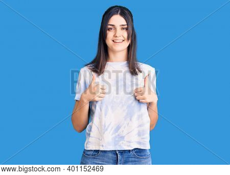 Young beautiful girl wearing casual t shirt success sign doing positive gesture with hand, thumbs up smiling and happy. cheerful expression and winner gesture.