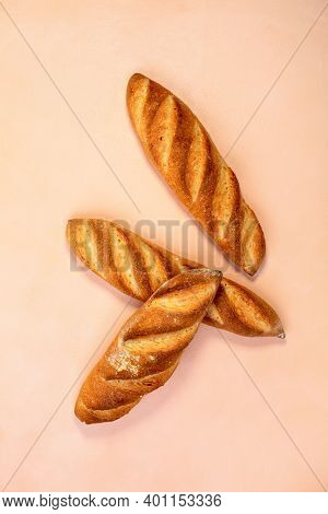 Three Artisanal French Mini Baguettes On Sourdough With Golden Crispy Crust On The Background Of The