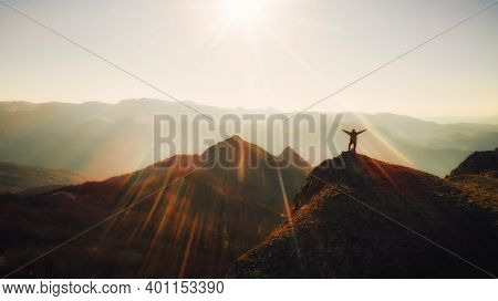 Grateful Person Standing At The Top Of The Mountain At Sunset.reaching The Peak. Business Achievemen