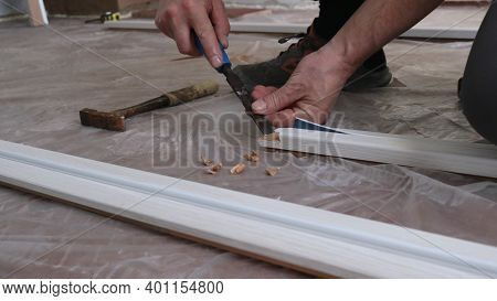 Male Hands Professionally Working With A Chisel On The Wooden Slats Of The Door Frame In Preparation