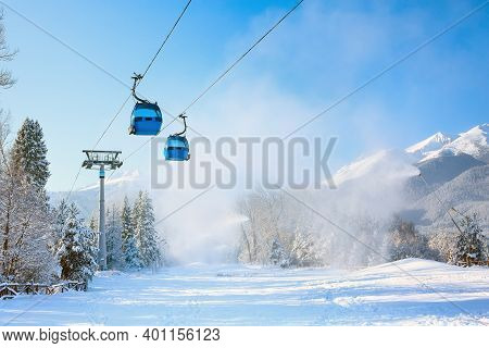 Bansko, Bulgaria Winter Ski Resort Panorama With Blue Gondola Lift Cabins, Forest Pine Trees, Pirin