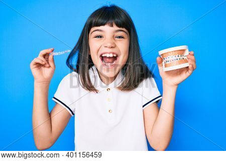 Young little girl with bang holding invisible aligner orthodontic and braces smiling and laughing hard out loud because funny crazy joke.