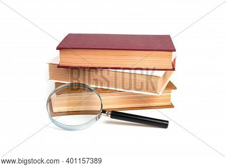 Stack Of Books, Textbooks With Magnifying Glass Isolated On White Background.