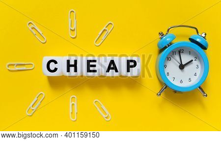 Finance And Economics Concept. On A Yellow Background, A Blue Alarm Clock, Paper Clips And White Cub