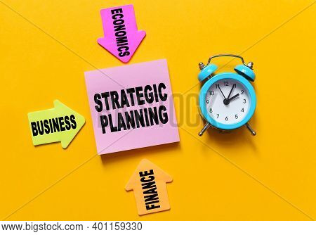 Finance And Economics Concept. On A Yellow Background, A Blue Alarm Clock, Multi-colored Paper Arrow