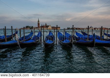 Docked Gondola Float In The Waters Near St Mark's Square, With The Bell Tower Of The Church Of San G