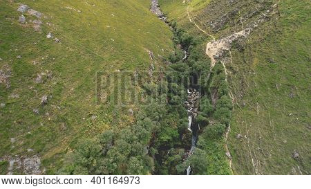 Green mountains path aerial. Rock mount stream river banks. Narrow way from hill to cloudy peak. Cinematic nobody nature landscape of Arran Island, Scotland. Summer vacation at greenery ranges