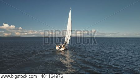 Closeup yacht cruise at open sea aerial. Regatta on luxury sailboat at bay. Picturesque seascape of ocean harbor. Brodick pier, Arran Island, Scotland, Europe. Amazing nature landscape at summer day