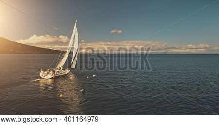 Sun over sailing regatta on luxury yachts aerial. Cinematic seascape of yachting summer sunny day. Majestic sail boats race at ocean bay in Brodick harbour, Arran Island, Scotland. Panorama drone shot