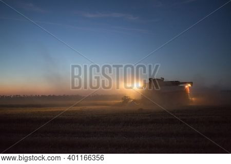 Farm Is Harvesting At Night. Several Harvesters Harvest Wheat On A Summer Night. Night View Of Harve