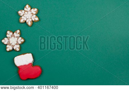Santa Claus Boots And Snowflakes On A Green Background. Christmas Gingerbread In The Form Of Boots A