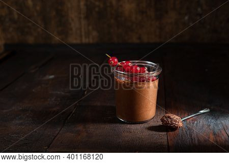 A Teaspoon With Chocolate Mousse, A Glass With Chocolate Mousse And Red Currant Berries On The Dark