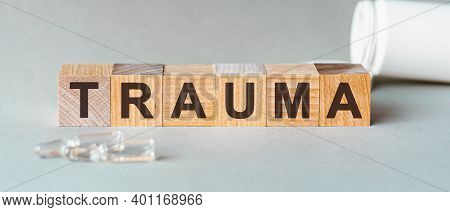 Trauma Is A Word Written In Black Letters On Wooden Cubes, Grey Background. Trauma Text On Wooden Bl