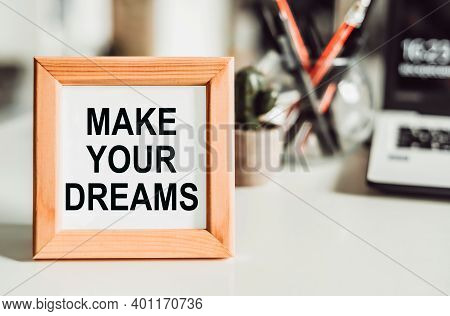 Wooden Frame With Office Background With Text - Make Your Dreams. The Concept Of The Desire To Keep