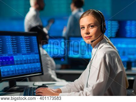 Diverse team of brokers workin in office using workstation and analysis technology. Workplace of professional traders. Global financial markets, business strategy, currency exchange and banking.