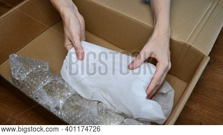 Woman Hands Pack Up Fragile Tableware Into Wrapping Bubble Plastic And Put Into Cardboard Box In Pre