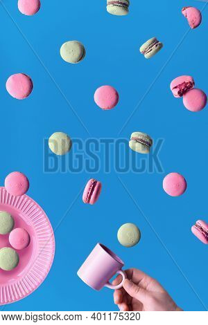 Levitation Of Macaroons, Creative Food Concept. Flying Macaroons On A Plate And Around. Hand With Co
