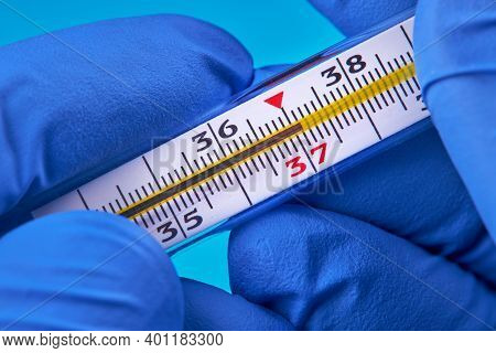 Person In Medical Gloves Holds Mercury Thermometer That Show 37 Temperature. Temperature And Fever C