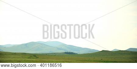 Panoramic Shot Of A Long Steppe With A Mountain Peak In The Background.