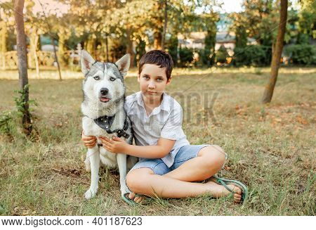 Little Boy Playing With His Beautiful Dog Outdoors Enjoying Together. Best Friends Rest And Have Fun