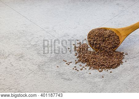 Flax Seeds In A Wooden Spoon On A Gray Concrete Background, A Dietary Product That Reduces Cholester