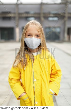 Little Caucasian Girl 7 Years Old With Blonde Hair In Yellow Raincoat And Face Mask During Coronavir