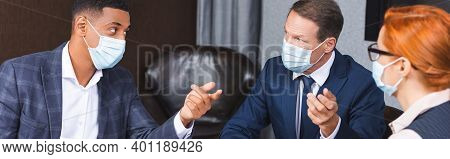Multicultural Businesspeople In Medical Masks Gesturing During Discussion Near Female Colleague In B