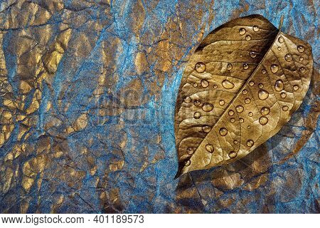 Gold Leaf In Water Drops On Blue And Gold Pastel Background. Gold And Blue Abstract Background. Phot