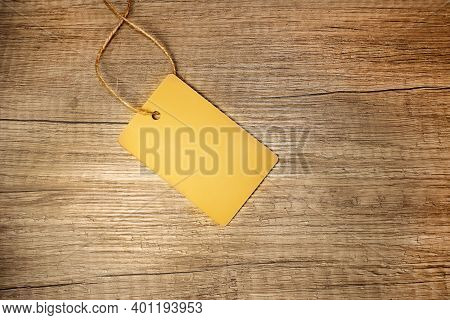 Yellow Empty Tag With Rope On Wooden Surface. Price Tag, Gift Tag, Sale Tag, Address Label